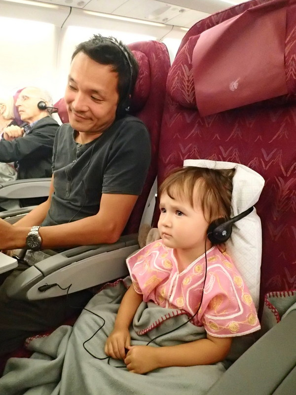 Engrossed in a cartoon. Putting the pillow behind her head helps to keep the headphones on!